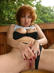 Redhead granny plays with her pair of big breasts while cramming a huge dildo inside her bald pussy